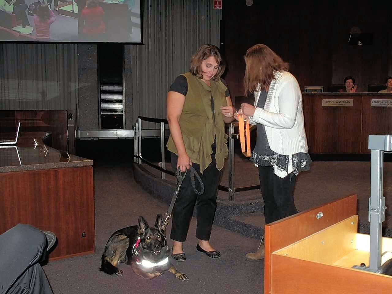 "Monica Prestifilipo, a leader in the Naperville running community, donates her ""legacy medal"" from the Healthy Driven Naperville Half Marathon to Mina, a service dog who completed the race with Debbie Mossburg, a cancer survivor who founded a childhood cancer support charity called Bike Bald."