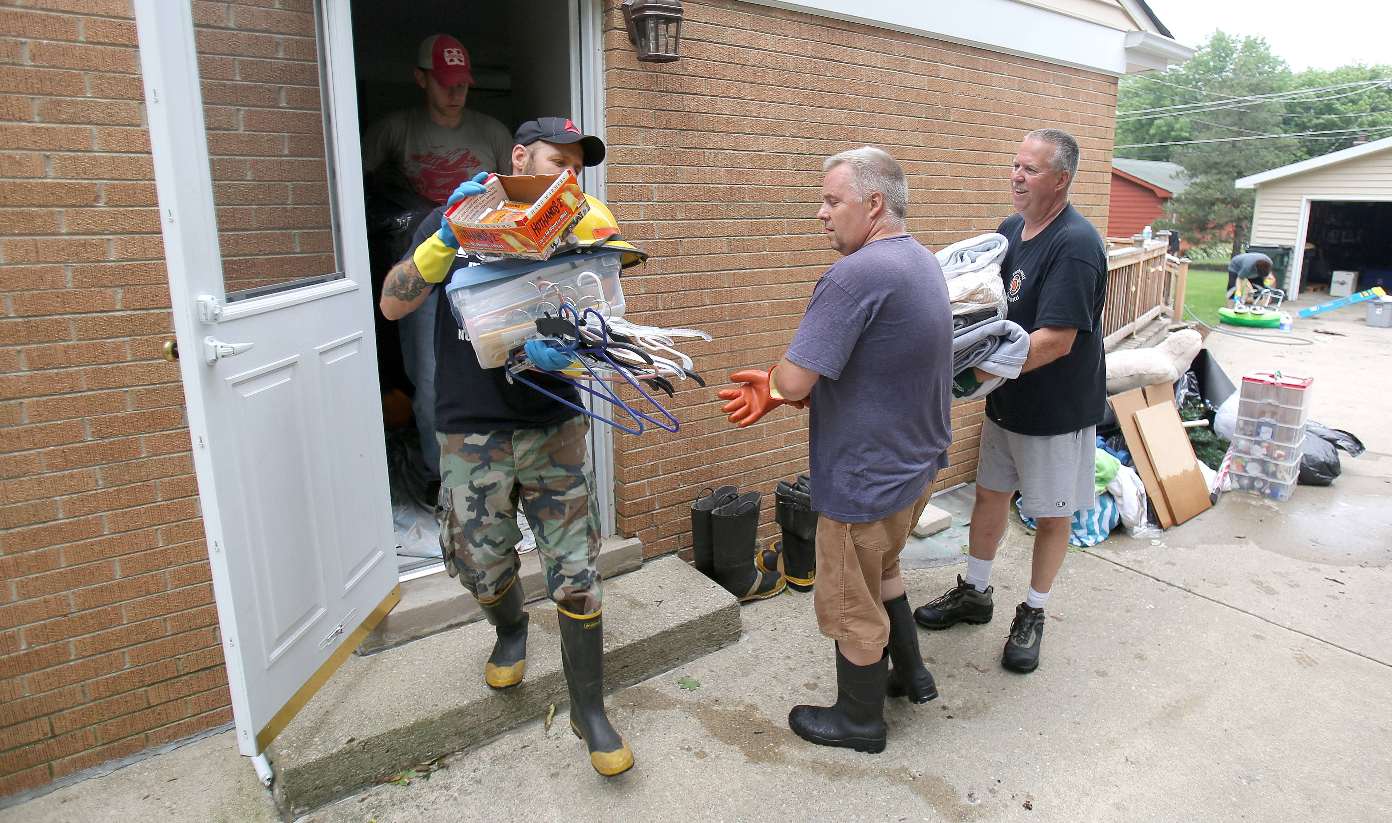 Steve Lundy/slundy@dailyherald.comLibertyville residents help a neighbor clean up after Wednesday's flooding.