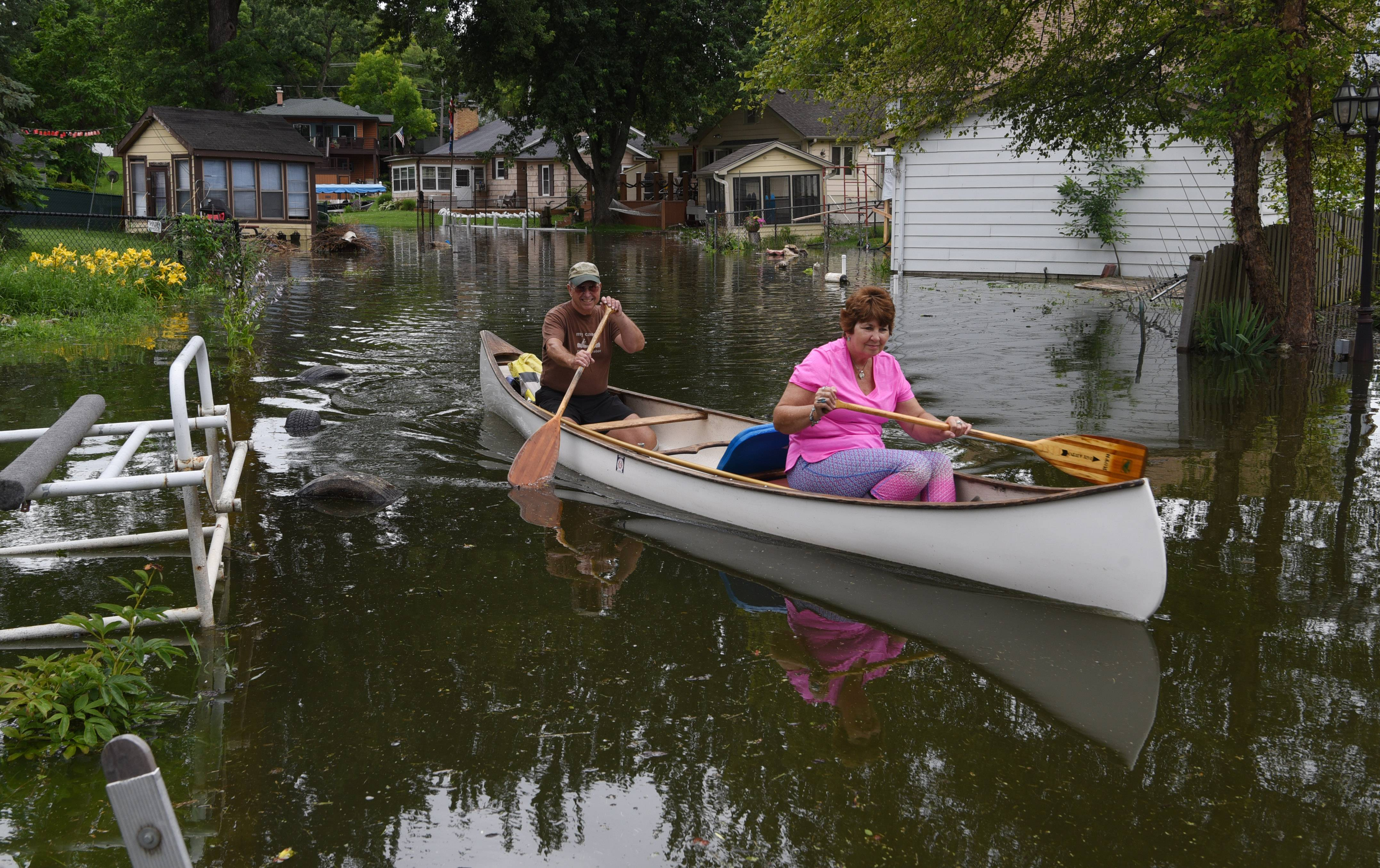 Joe Lewnard/jlewnard@dailyherald.comLouis Igyarto and his wife Ruth paddle their canoe on the channel behind their Fox Lake home, where they been living for 25 years. They are adjacent to the water, and although there is a chance of flooding, they enjoy living there.