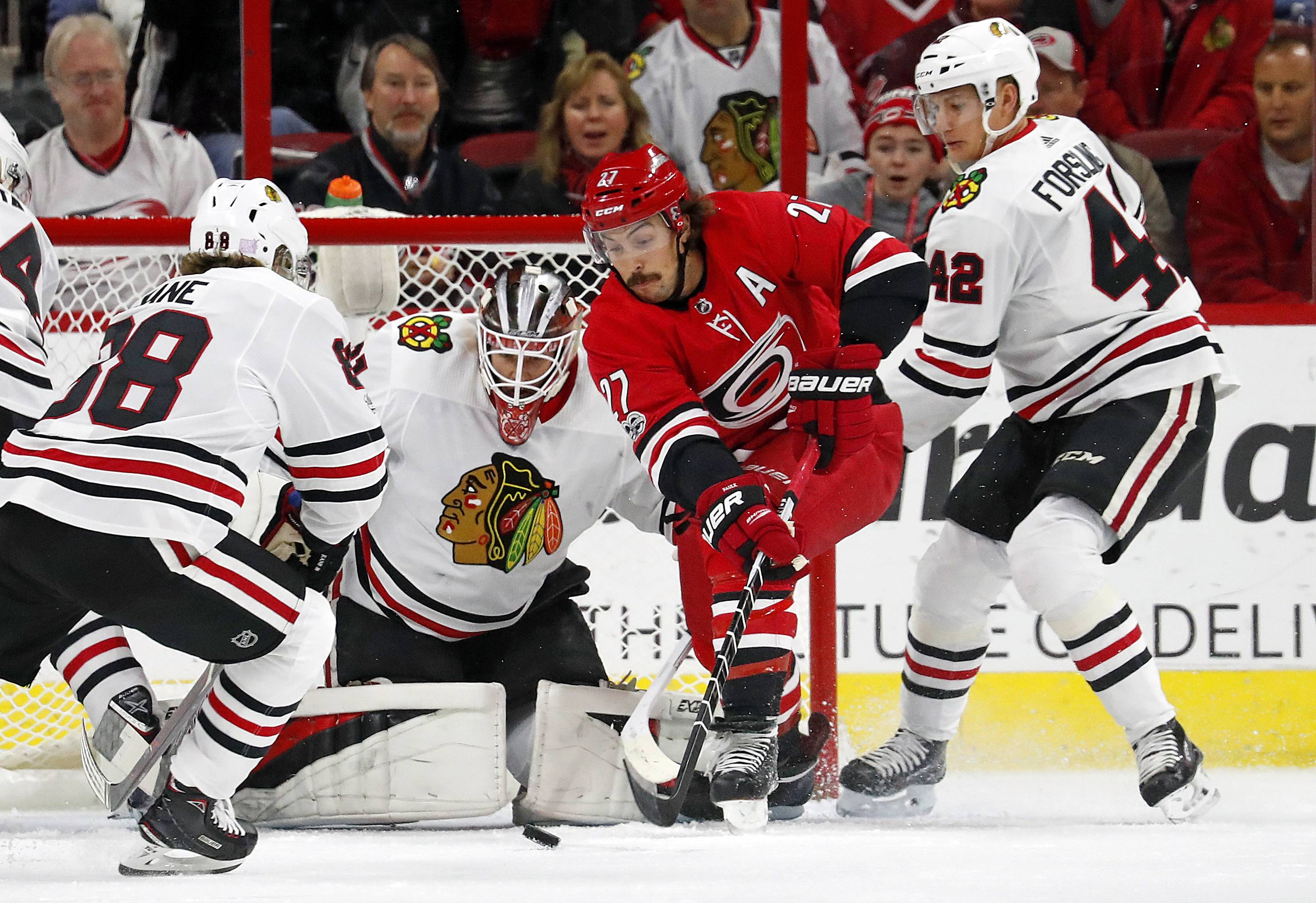 Carolina Hurricanes' Justin Faulk (27) works the puck in front of Chicago Blackhawks' goalie Anton Forsberg (31) between Blackhawks' Patrick Kane (88) and Gustav Forsling (42) during the first period of an NHL hockey game, Saturday, Nov. 11, 2017, in Raleigh, N.C. (AP Photo/Karl B DeBlaker)