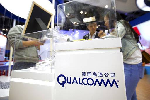 FILE - In this Thursday, April 27, 2017, file photo, visitors look at a display booth for Qualcomm at the Global Mobile Internet Conference (GMIC) in Beijing. On Monday, Nov. 13, 2017, Qualcomm said they are rejecting an unsolicited offer from Broadcom, saying that the proposal is significantly undervalued and that a tie-up between the massive chipmakers would face substantial regulatory resistance. (AP Photo/Mark Schiefelbein, File)
