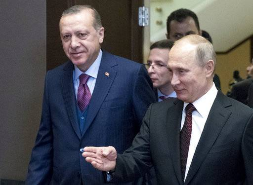 Russian President Vladimir Putin, right, welcomes Turkish President Recep Tayyip Erdogan as they enter a hall during their meeting in the Bocharov Ruchei residence in the Black Sea resort of Sochi, Russia, Monday, Nov. 13, 2017. (AP Photo/Pavel Golovkin, Pool)