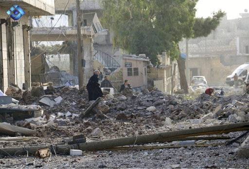 This image released by Thiqa News Agency shows people inspecting damage from airstrikes on Atareb, in the opposition-held countryside outside Aleppo Syria, Monday, Nov. 13, 2017. Syrian activists say at least 16 people have been killed in an airstrike on the market in a town in the north of the country. (Thiqa News via AP)