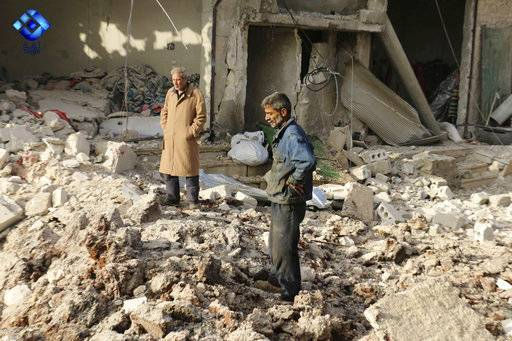 This image released by Thiqa News Agency shows people inspecting damage from airstrikes hit in Atareb town, in the western Aleppo countryside, of Syria, Monday, Nov. 13, 2017. Syrian activists say at least 16 people have been killed in the airstrike on the market town in the north of the country. (Thiqa News via AP)