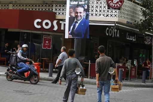 "A poster of resigned Lebanese Prime Minister Saad Hariri with Arabic that read, ""We are all with you,"" hangs on a street in Beirut, Lebanon, Monday, Nov. 13, 2017. Cardinal Bechara el-Rai, who heads the Maronite sect, Lebanon's biggest Christian community and the Middle East's largest Catholic church, is to head to Saudi Arabia and is expected to meet with Hariri, in a visit he had planned before Hariri announced his resignation. (AP Photo/Hassan Ammar)"