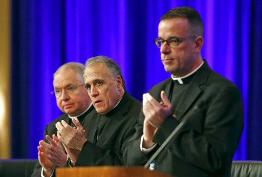 Los Angeles Archbishop Jose Gomez, from left, vice president of the United States Conference of Catholic Bishops, Cardinal Daniel DiNardo of the Archdiocese of Galveston-Houston, conference president, and Rev. J. Brian Bransfield, conference general secretary, applaud after a speech by Archbishop Christophe Pierre, Apostolic Nuncio to the United States, at the USCCB's annual fall meeting in Baltimore, Monday, Nov. 13, 2017.