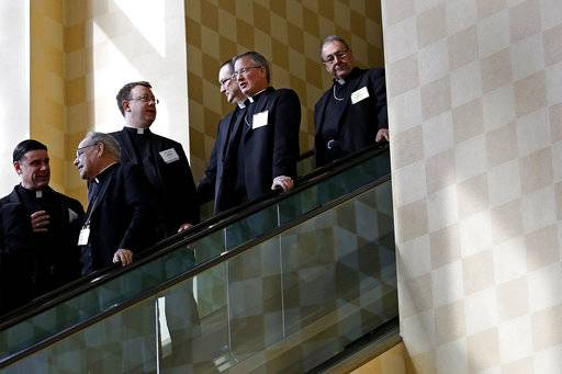 Members of the the United States Conference of Catholic Bishops ride an escalator during a break in sessions at the USCCB's annual fall meeting in Baltimore, Monday, Nov. 13, 2017.