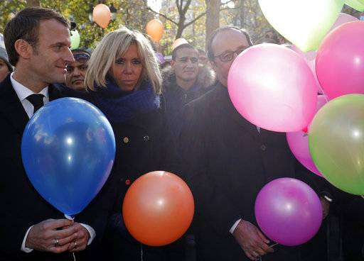French President Emmanuel Macron, left, his wife Brigitte, and former French President Francois Hollande prepare to release balloons at Paris 11th district town hall, Monday, Nov. 13, 2017, during a ceremony held for the victims of the Paris attacks. Multicolored balloons are taking to sunny skies above Paris in honor of the 130 victims of attacks on the Bataclan concert hall, Paris cafes and the national stadium to mark the 2nd anniversary of the worst terror attacks in France. (Philippe Wojazer, Pool via AP)
