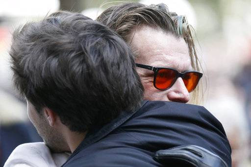 Jesse Hughes, right, lead singer of the US band Eagles of Death Metal, attends a ceremony marking the second anniversary of the Paris attacks at the Bataclan concert Hall, Monday Nov.13 2017. In silence and tears, families of France's deadliest terrorist attacks stood alongside President Emmanuel Macron to honor the 130 people killed two years ago Monday, when Islamic State extremists attacked the City of Light. The Eagles of Death Metal were performing that night at the Bataclan. (Etienne Laurent, Pool via AP)