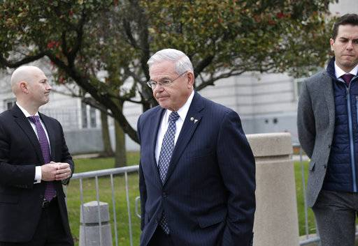 "Democratic U.S. Sen. Bob Menendez, center, leaves the federal courthouse in Newark, N.J., Monday, Nov. 13, 2017. Jurors in the bribery trial of Menendez have sent the judge a note saying they ""can't reach a unanimous verdict on any of the charges."" The judge has excused the jurors for the day and told them to return Tuesday to continue deliberating. (AP Photo/Seth Wenig)"