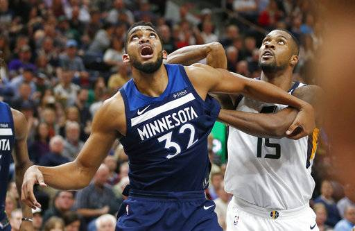 Minnesota Timberwolves center Karl-Anthony Towns (32) and Utah Jazz forward Derrick Favors (15) battle under the boards for a rebound in the second half during an NBA basketball game Monday, Nov. 13, 2017, in Salt Lake City. (AP Photo/Rick Bowmer)