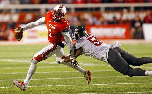 Utah quarterback Tyler Huntley (1) eludes the tackle from Washington State linebacker Frankie Luvu (51) in the second half of an NCAA college football game Saturday, Nov. 11, 2017, in Salt Lake City. (AP Photo/Rick Bowmer)