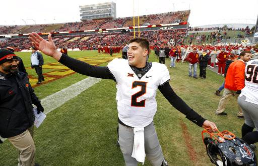 Oklahoma State quarterback Mason Rudolph celebrates as he walks off the field after an NCAA college football game against Iowa State, Saturday, Nov. 11, 2017, in Ames, Iowa. Oklahoma State won 49-42. (AP Photo/Charlie Neibergall)