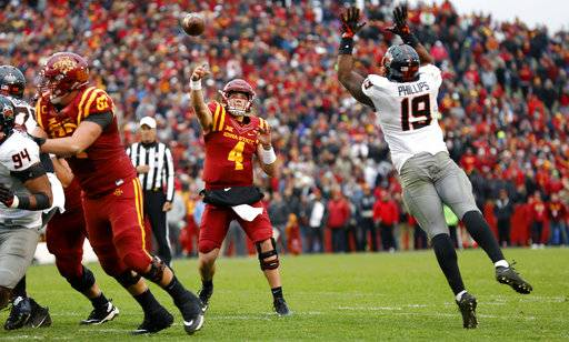 Iowa State quarterback Zeb Noland (4) throws a pass over Oklahoma State linebacker Justin Phillips (19) during the second half of an NCAA college football game, Saturday, Nov. 11, 2017, in Ames, Iowa. Oklahoma State won 49-42. (AP Photo/Charlie Neibergall)