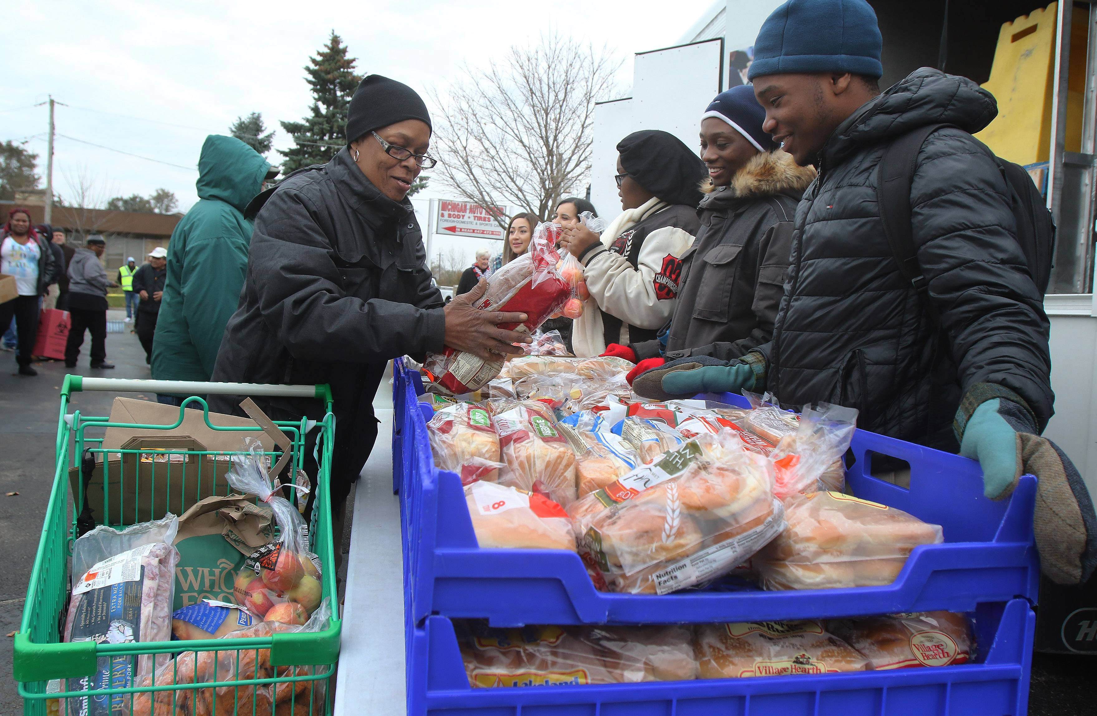 Former Army Sgt. Lolita Shelton of North Chicago picks up bread from volunteers Jacquolin Nutall and Tailor Woods, both of Waukegan, as they hand out food Tuesday at Midwest Veterans Closet in North Chicago. The organization and the Northern Illinois Food Bank provided food and coats and clothing to military veterans and their families.