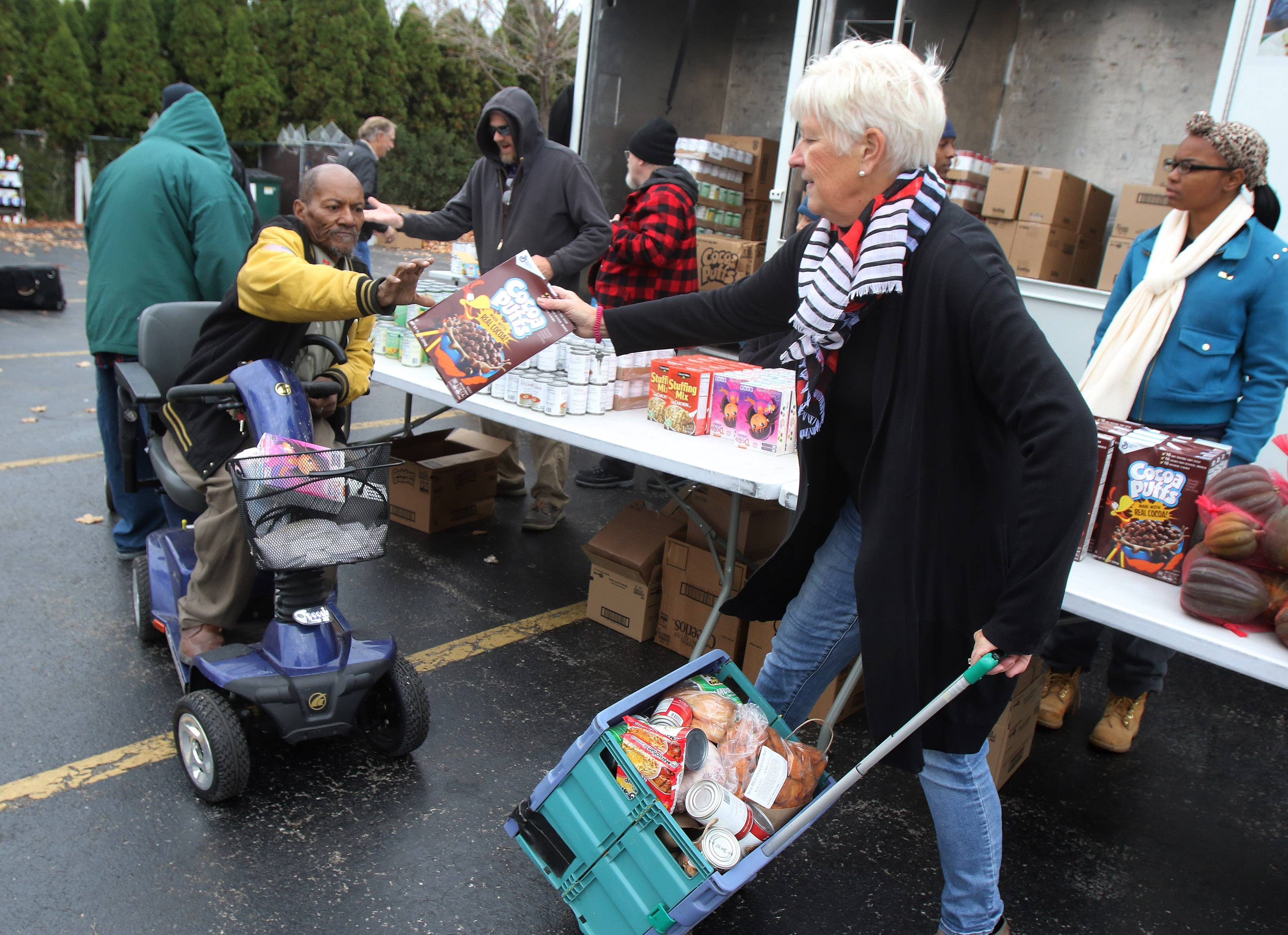 Midwest Veterans Closet Food Pantry Director Barb Karacic, right, helps Johnnie Beard of North Chicago collect food Tuesday in North Chicago. The organization and the Northern Illinois Food Bank provided food and coats and clothing to military veterans and their families.