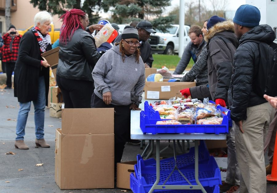 Army veteran Tami Thweatt of Waukegan picks up some bread from volunteers as they hand out food Tuesday at Midwest Veterans Closet in North Chicago. The organization and the Northern Illinois Food Bank provided food and coats and clothing to military veterans and their families.