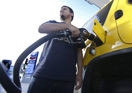 FILE - In this Monday, Oct. 30, 2017, file photo, Cristian Rodriguez fuels his vehicle in Sacramento, Calif. The price of oil has risen by about one-third since the summer, but many experts think the surge won't last. They point to growing U.S. production. Still, higher prices for energy could translate into higher prices for airline tickets and consumer goods.