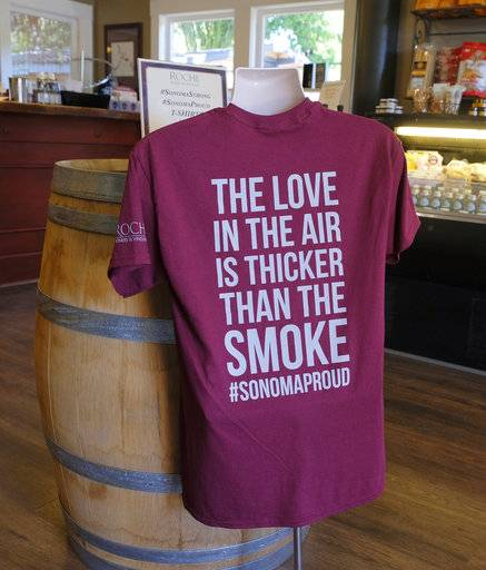 In this photo taken Saturday, Oct. 28, 2017, a t-shirt referencing the recent wildfires is shown for sale in the tasting room at Roche Winery and Vineyards in Sonoma, Calif. The impact the wildfires had on the wine industry was minimal overall, but many face challenges making up for losses sustained during closures at the busiest time of year and now convincing people to revisit.