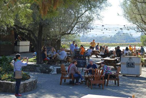 In this photo taken Saturday, Oct. 28, 2017, people fill a patio tasting wine and listening to music at the historic Gundlach Bundschu winery in Sonoma, Calif. A month after deadly wildfires swept through California's famed wine country, hot air balloons at sunrise are floating again over vineyards and nearly everything is now open. The impact the fires had on the wine industry was minimal overall, but many face challenges making up for losses sustained during closures at the busiest time of year and now convincing people to revisit.