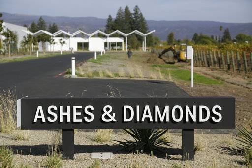 This photo taken Monday, Oct. 30, 2017, shows a sign and roadway leading to the new Ashes & Diamonds winery in Napa, Calif. A month after deadly wildfires swept through California's famed wine country, hot-air balloons are floating again over Napa Valley vineyards splashed with fall colors. On the heels of the disaster, a new winery is opening, keeping the name it chose some time ago: Ashes & Diamonds.