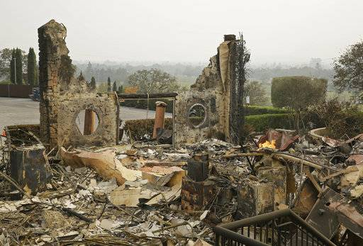 FILE - In this Oct. 10, 2017 file photo, the remains of the Signorello Estate winery continue to smolder in Napa, Calif. A month after deadly wildfires swept through California's famed wine country. Lost in the fire was the Napa winery's signature stone hospitality building. A kitchen, corporate offices, a wine lab and the home of owner Ray Signorello Jr. also were destroyed.