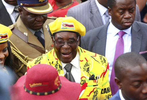 "FILE -- In this Wednesday, Nov. 8, 2017 file photo, Zimbabwean President Robert Mugabe, centre, arrives for a solidarity rally in Harare.  Armored personnel carriers were seen Tuesday Nov. 14, 2017, outside the capital a day after the army commander Chiwenga threatened to ""step in"" to calm political tensions over the president's firing of his deputy."