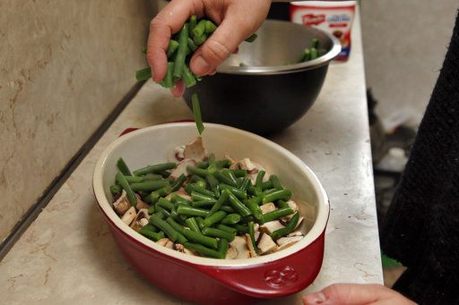 Ruthy Kirwan, of Percolate Kitchen, puts a layer of the fresh cut, blanched green beens on the sliced mushrooms in the gratin dish, as she prepares her version of the classic Thanksgiving favorite Green Been Casserole, in her apartment kitchen in the Queens borough of New York, Wednesday, Nov. 8, 2017. Before actors perform a play for an audience, they run a dress rehearsal to look for kinks that need fixing before the show opens. Traditional Thanksgiving dinner is a big production that can benefit from rehearsal, too, say some veteran hosts.