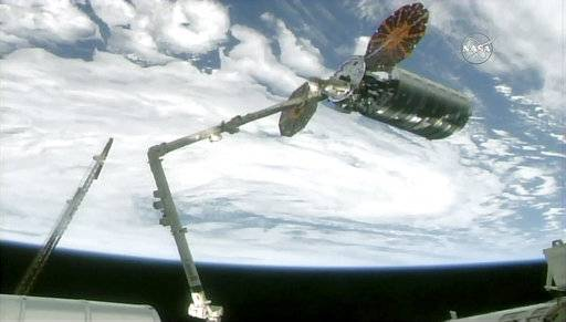 The International Space Station's robotic arm captures the Cygnus cargo spacecraft, Tuesday, Nov. 14, 2017, 260 miles  (418 kms.) above the earth. The commercial supply ship arrived at the International Space Station on Tuesday, two days after launching from Virginia. (NASA TV via AP)