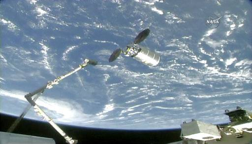 The International Space Station's robotic arm reaches to capture the Cygnus cargo spacecraft, Tuesday, Nov. 14, 2017, 260 miles (418 kms.) above the earth. The commercial supply ship arrived at the International Space Station on Tuesday, two days after launching from Virginia. (NASA TV via AP)