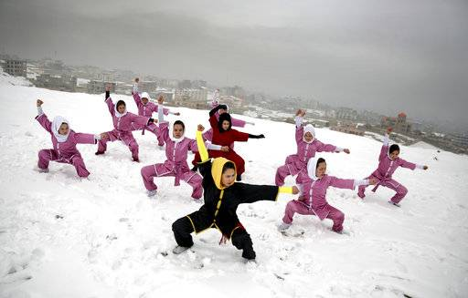 "FILE - In this Jan. 25, 2017 file photo, Shaolin martial arts students follow their trainer, Sima Azimi, 20, in black, during a training session on a hilltop in Kabul, Afghanistan. The annual survey by the San Francisco-based Asia Foundation, released Tuesday, Nov. 14, 2017, has found that Afghans are slightly more optimistic about the future than they were last year, despite a stagnant economy and near-constant attacks by a revitalized Taliban. The foundation acknowledged that the slight increase in optimism is ""difficult to explain.�"