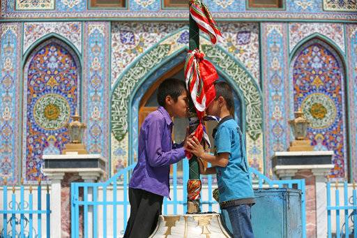 "FILE - In this Sept. 11, 2017 file photo, Afghan Shiite boys kiss a holy mace to bring blessings, at the Karti Sakhi shrine, in Kabul, Afghanistan. The annual survey by the San Francisco-based Asia Foundation, released Tuesday, Nov. 14, 2017, has found that Afghans are slightly more optimistic about the future than they were last year, despite a stagnant economy and near-constant attacks by a revitalized Taliban. The foundation acknowledged that the slight increase in optimism is ""difficult to explain.�"