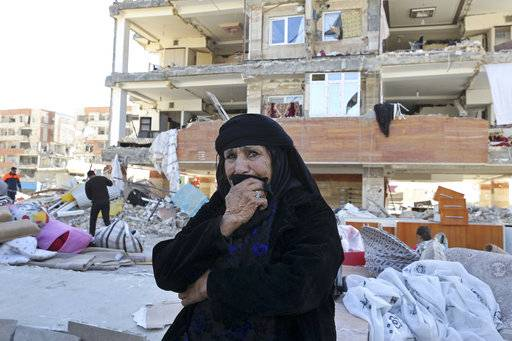 An earthquake survivor weeps as she sits in front of damaged buildings, in a compound which was built under the Mehr state-owned program, in Sarpol-e-Zahab in western Iran, Tuesday, Nov. 14, 2017. Iran's President Hassan Rouhani says his administration will probe the cause of so much damage to buildings constructed under the Mehr program after a powerful earthquake hit the area along the border with Iraq on Sunday which killed over 400 people.
