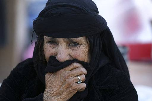 An earthquake survivor weeps in front of her house in a compound which was built under the Mehr state-owned program, in Sarpol-e-Zahab in western Iran, Tuesday, Nov. 14, 2017. Iran's President Hassan Rouhani says his administration will probe the cause of so much damage to buildings constructed under the Mehr program after a powerful earthquake hit the area along the border with Iraq on Sunday which killed hundreds of people.