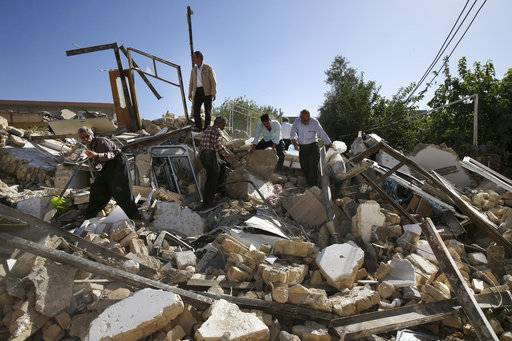 Earthquake survivors remove debris to salvage their belongings in Sarpol-e-Zahab in western Iran, Tuesday, Nov. 14, 2017. A powerful earthquake hit the area along the border with Iraq on Sunday and killed over 400 people.