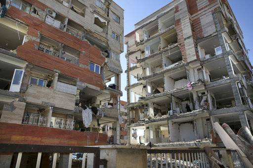 Buildings are damaged by an earthquake in a compound which was built under the Mehr state-owned program, in Sarpol-e-Zahab in western Iran, Tuesday, Nov. 14, 2017. Iran's President Hassan Rouhani says his administration will probe the cause of so much damage to buildings constructed under the Mehr program after a powerful earthquake hit the area along the border with Iraq on Sunday which killed over 400 people.