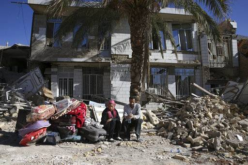 Survivors sit in front of a destroyed house on the earthquake site in Sarpol-e-Zahab in western Iran, Tuesday, Nov. 14, 2017. Rescuers are digging through the debris of buildings felled by the Sunday earthquake in the border region of Iran and Iraq.
