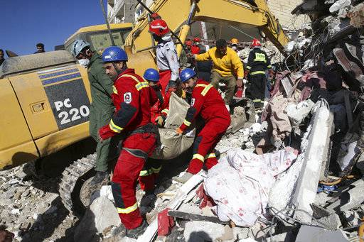 Rescuers carry away the body of an earthquake victim in Sarpol-e-Zahab in western Iran, Tuesday, Nov. 14, 2017. Rescuers are digging through the debris of buildings felled by the Sunday earthquake that killed more than four hundreds of people in the border region of Iran and Iraq.