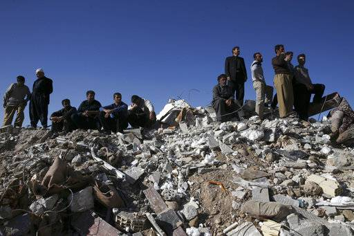 Survivors sit on the debris while rescuers search on the earthquake site in Sarpol-e-Zahab in western Iran, Tuesday, Nov. 14, 2017. Rescuers on Tuesday used backhoes and heavy equipment to dig through the debris of buildings toppled by a powerful earthquake on the border between Iran and Iraq.