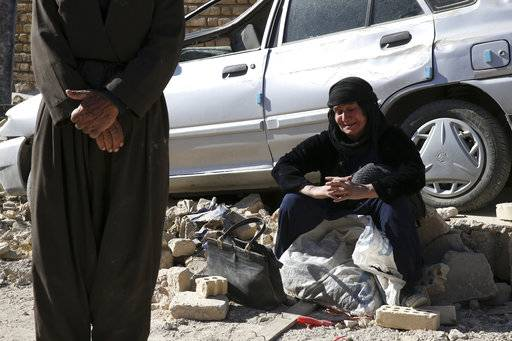 A woman sits on the debris on the earthquake site in Sarpol-e-Zahab in western Iran, Tuesday, Nov. 14, 2017. Rescuers are digging through the debris of buildings felled by the Sunday earthquake in the border region of Iran and Iraq.