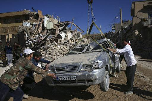 People and rescuers move a destroyed car on the earthquake site in Sarpol-e-Zahab in western Iran, Tuesday, Nov. 14, 2017. Rescuers are digging through the debris of buildings felled by the Sunday earthquake in the border region of Iran and Iraq.