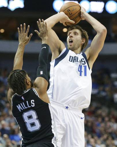 Dallas Mavericks forward Dirk Nowitzki (41), of Germany, shoots against San Antonio Spurs guard Patty Mills (8) during the first half of an NBA basketball game in Dallas, Tuesday, Nov. 14, 2017.