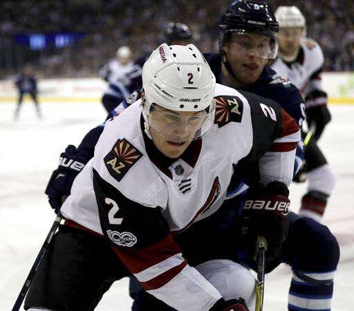 Arizona Coyotes' Luke Schenn (2) is driven towards the boards by Winnipeg Jets' Andrew Copp (9) during second period NHL hockey action in Winnipeg, Manitoba, Tuesday, Nov. 14, 2017. (Trevor Hagan/The Canadian Press via AP)