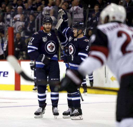 Winnipeg Jets' Adam Lowry (17)  and Andrew Copp (9) celebrate after Lowry scored against the Arizona Coyotes during second period NHL hockey action in Winnipeg, Manitoba, Tuesday, Nov. 14, 2017. (Trevor Hagan/The Canadian Press via AP)