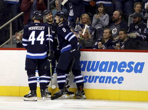 Winnipeg Jets' Josh Morrissey (44), Joel Armia (40) and Jacob Trouba (8) celebrate after Armia scored against the Arizona Coyotes during second period NHL hockey action in Winnipeg, Manitoba, Tuesday, Nov. 14, 2017. (Trevor Hagan/The Canadian Press via AP)