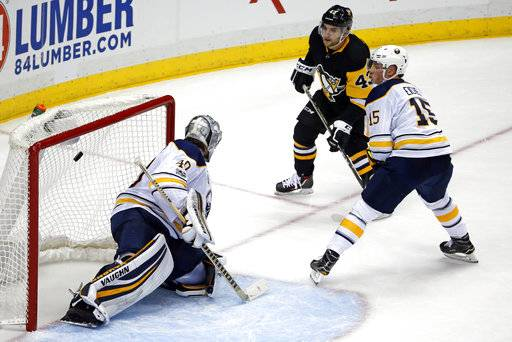 Pittsburgh Penguins' Conor Sheary (43) gets the game-winning overtime goal past Buffalo Sabres goalie Robin Lehner (40) with Jack Eichel (15) defending at the end of an NHL hockey game in Pittsburgh, Tuesday, Nov. 14, 2017. The Penguins won 5-4.