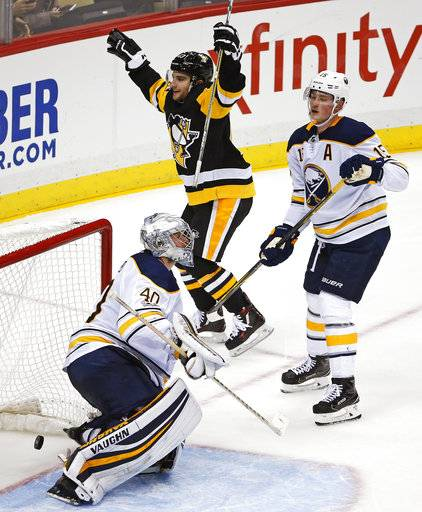 Pittsburgh Penguins' Conor Sheary (43) celebrates his game-winning overtime goal between Buffalo Sabres goalie Robin Lehner (40) and Jack Eichel (15) at the end of an NHL hockey game in Pittsburgh, Tuesday, Nov. 14, 2017. The Penguins won 5-4.