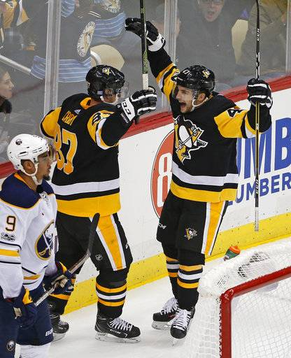 Pittsburgh Penguins' Conor Sheary (43) celebrates his game-winning overtime goal with Sidney Crosby (87) behind Buffalo Sabres' Evander Kane (9) at the end of an NHL hockey game in Pittsburgh, Tuesday, Nov. 14, 2017. The Penguins won 5-4.
