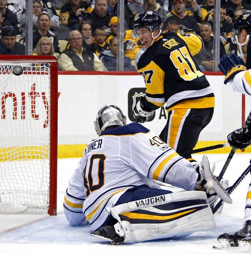 Pittsburgh Penguins' Sidney Crosby (87) lifts the puck over Buffalo Sabres goalie Robin Lehner (40) for a goal in the second period of an NHL hockey game in Pittsburgh, Tuesday, Nov. 14, 2017.