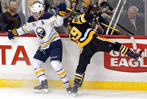 Pittsburgh Penguins' Jake Guentzel (59) collides with Buffalo Sabres' Jack Eichel (15) during the first period of an NHL hockey game in Pittsburgh, Tuesday, Nov. 14, 2017.